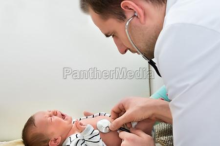 doctor examining crying baby
