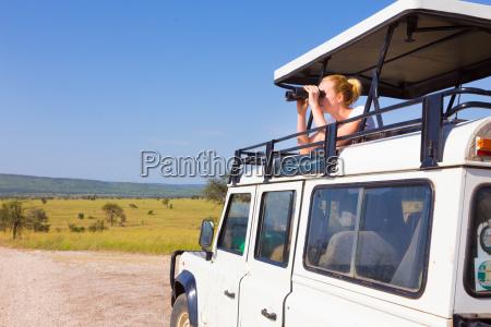 mujer en safari mirando a traves