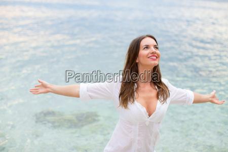 mujer relajandose en la playa con