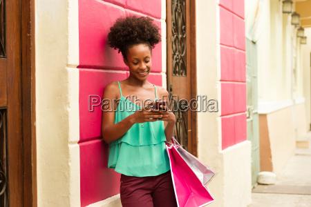 negro chica de compras y mensajes