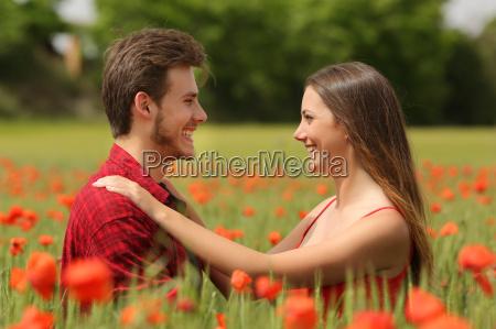 pareja mirandose carinyosamente en un campo
