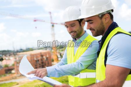 ingeniero y trabajador viendo blueprint en