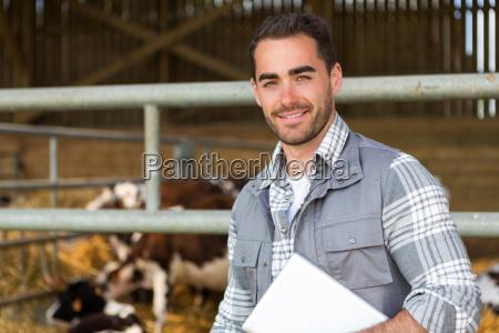 granjero atractivo joven en un granero