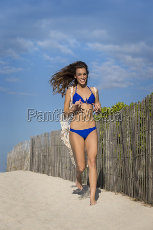 woman in blue bikini running at