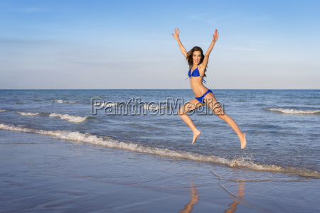 young cheerful woman in bikini jumping