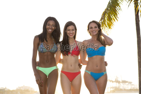 three women in bikini walking back