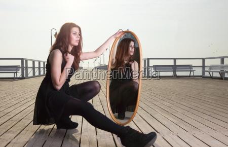 mujer reflexiva mira la reflexion en