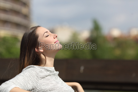 mujer urbana respirando aire fresco profundo