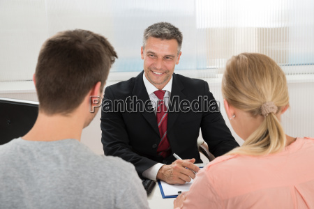 estate agent talking to couple in