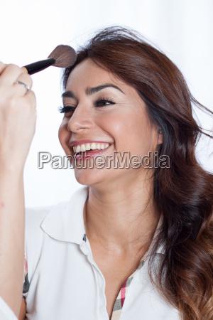 mujer sonriendo con un pincel de
