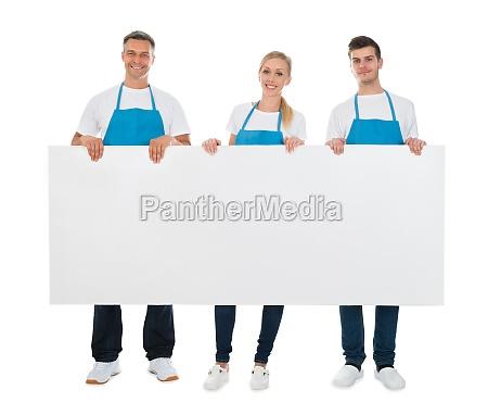 limpiadores sosteniendo en blanco cartelera