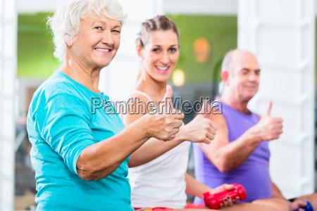 seniorer og traenere med handvaegte pa