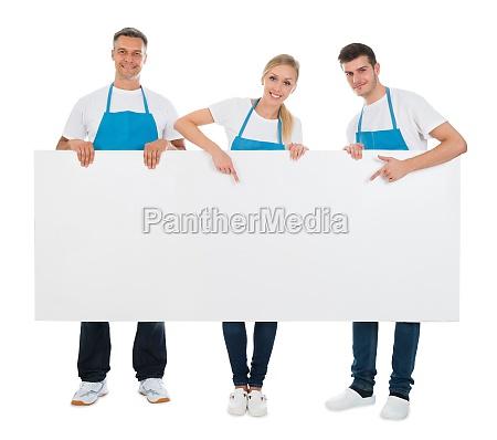 limpiadores que sostienen cartel en blanco