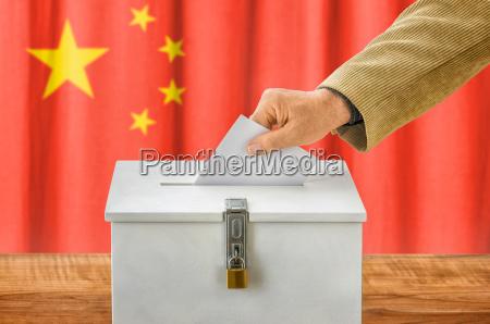 man putting ballot in ballot box