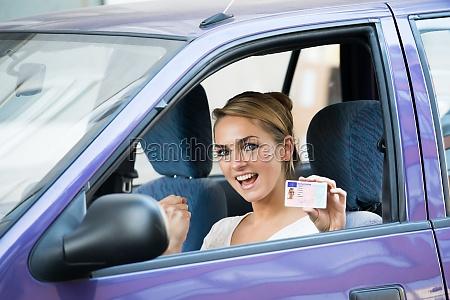 mujer mostrando licencia mientras se sienta