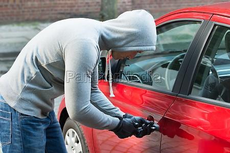 ladron en chaqueta con capucha robando