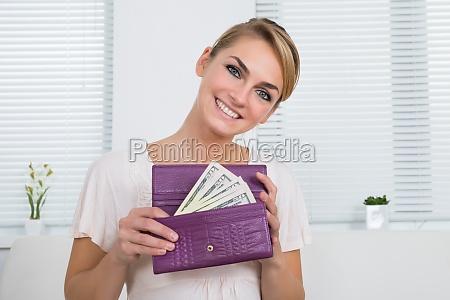 mujer feliz mostrando dinero en monedero