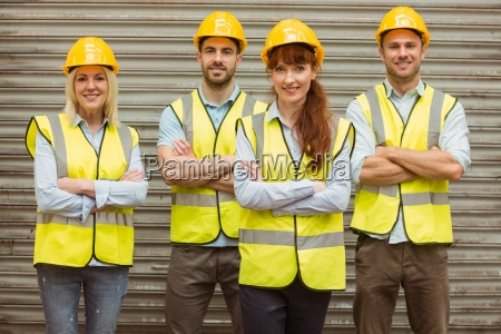 warehouse team with arms crossed wearing