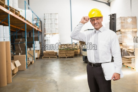 warehouse manager wearing hard hat holding