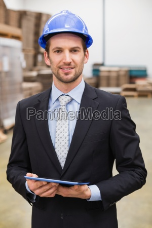 warehouse manager wearing hard hat using