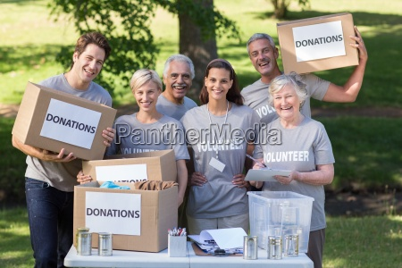 happy volunteer family holding donations boxes