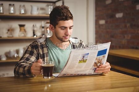 beber cafe y leyendo el periodico