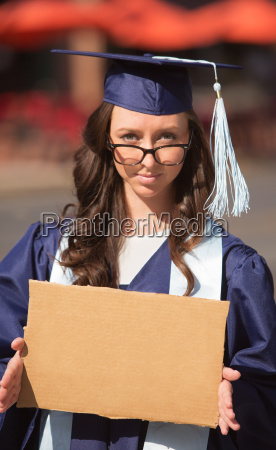 graduate carrying cardboard sign