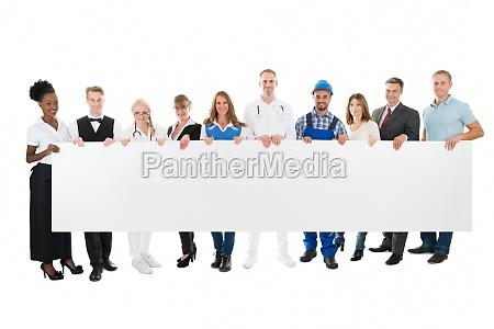 personas con diversas ocupaciones sosteniendo cartelera