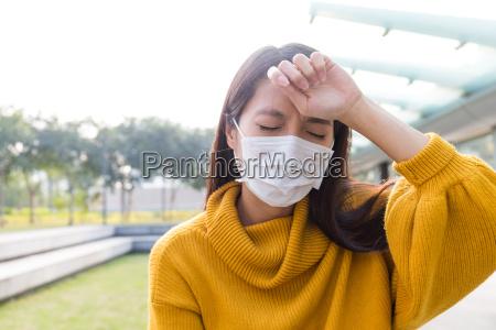 mujer vistiendo la mascarilla y sintiendo