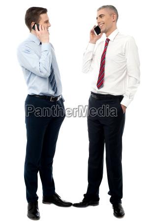 two male entrepreneur talking on mobile