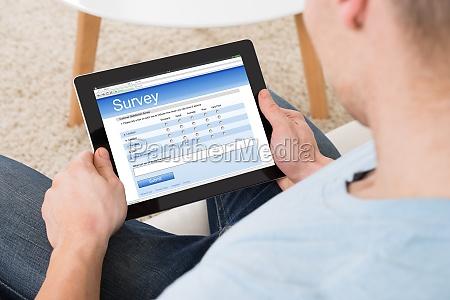 man filling survey form online on