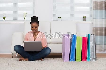 woman sitting on carpet shopping online
