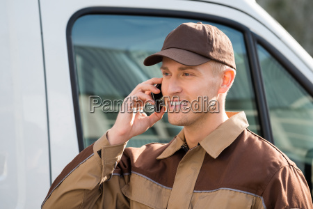 smiling delivery man using mobile phone