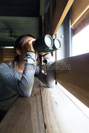 mujer que usa binoculares para observar