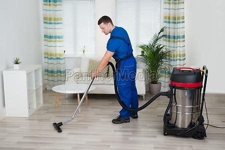 trabajador limpieza piso con aspirador en