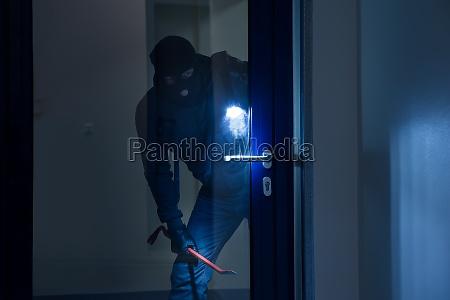 ladron con linterna tratando de romper