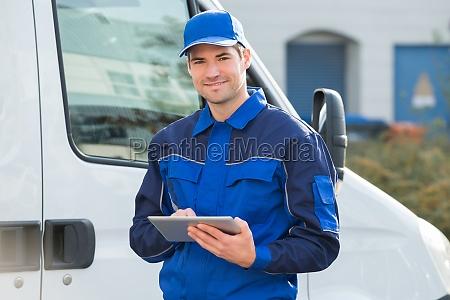 repartidor sonriendo usando tableta digital por