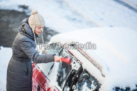 mujer joven limpiando su coche de