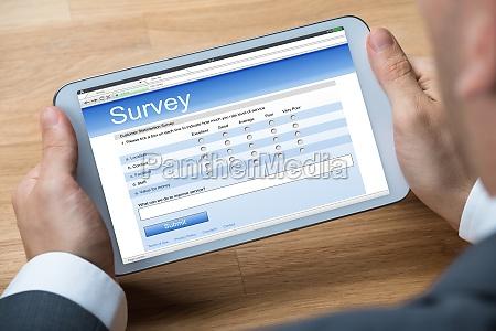 businessman giving online survey on digital