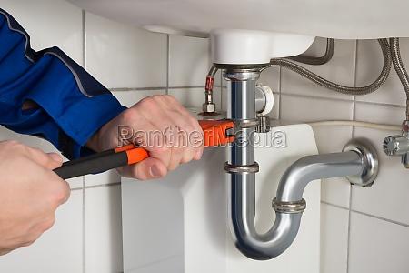 hombre fontanero reparacion fregadero en el