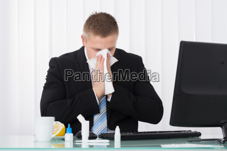 enfermo empresario soplando su nariz