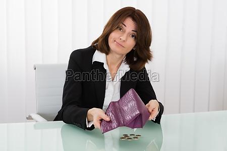 businesswoman sosteniendo monedero vacio con monedas