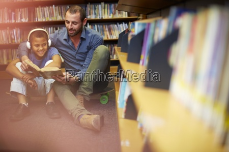 man reading book to boy with