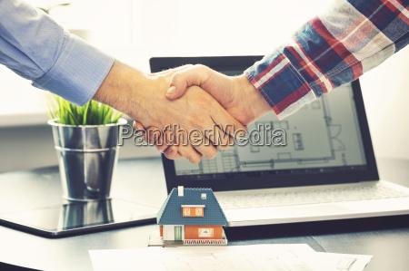 agente inmobiliario sacudiendo las manos con