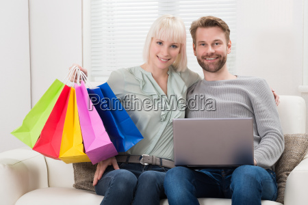 couple holding shopping bag with laptop