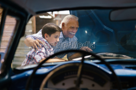 boy with grandpa looking car engine