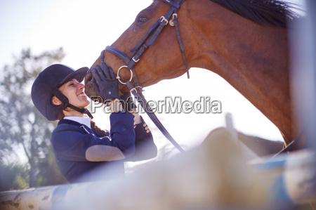 mujer joven sonriente con caballo en