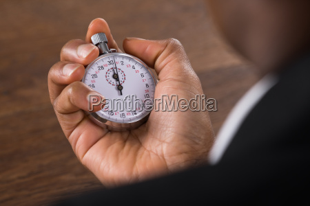 businessperson holding reloj de detencion