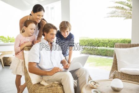 familia usando la computadora portatil en