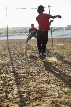 chicos jugando futbol juntos en el